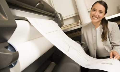Female architect looking at a technical document --- Image by © Somos Images/Corbis